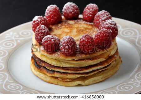 round cake of several layers with raspberries dusted with powdered sugar on dark background