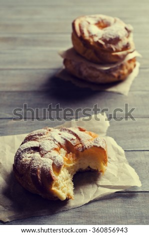 Round cake with cream, sprinkle with powdered sugar,  on a wooden background. Selective focus.