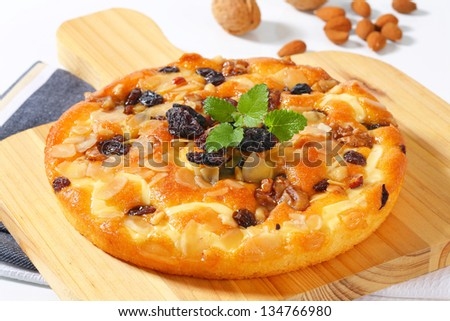 round cake with nuts and raisins on a wooden cutting board - stock photo