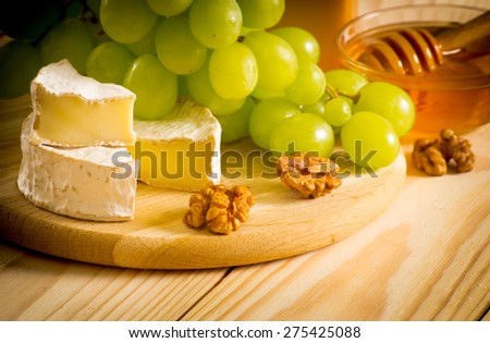 Round camembert cheese, honey, walnuts and grapes on the wooden board. For this photo applied vignetting effect.