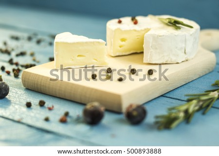 Round camembert cheese mold with rosemary on the wooden board