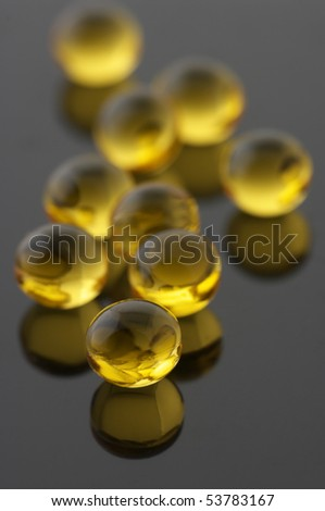 Round capsules with vitamins A&E on gray background. - stock photo