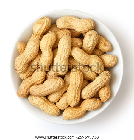 Round ceramic bowl of peanuts in shells. From above. - stock photo