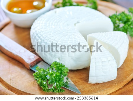 round cheese and aroma spice on wooden board - stock photo