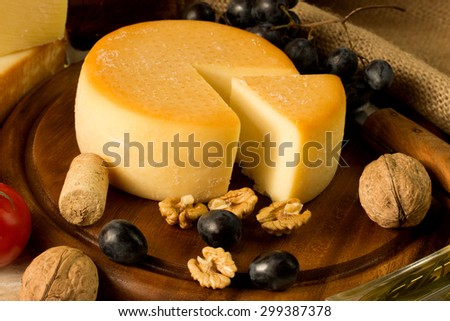 round cheese on a cutting board, with nut and grape - stock photo