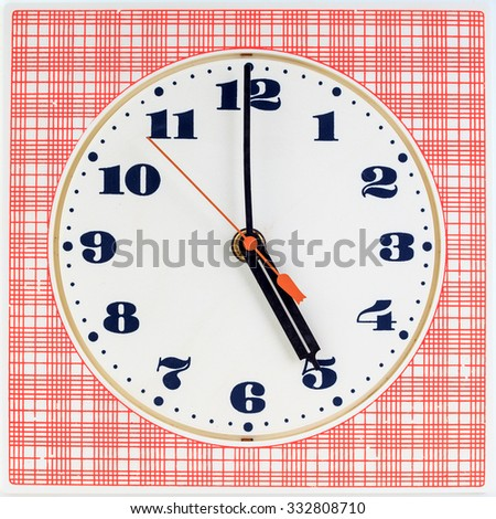 Round clock face on red striped background showing five o'clock - stock photo