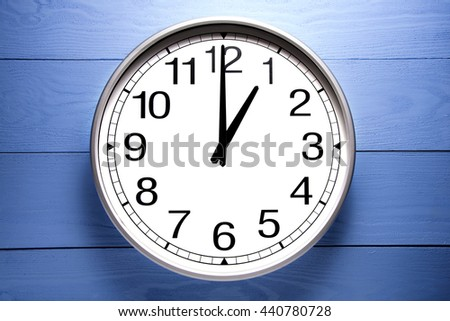 Round clock shows shows at 1 o'clock, clock on blue background - stock photo