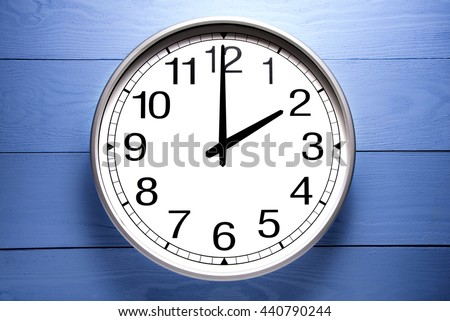 Round clock shows shows at 2 o'clock, clock on blue background - stock photo