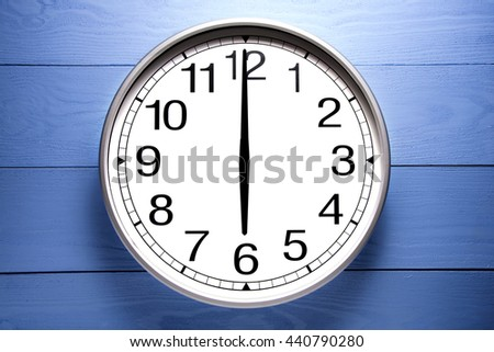 Round clock shows shows at 6 o'clock, clock on blue background - stock photo