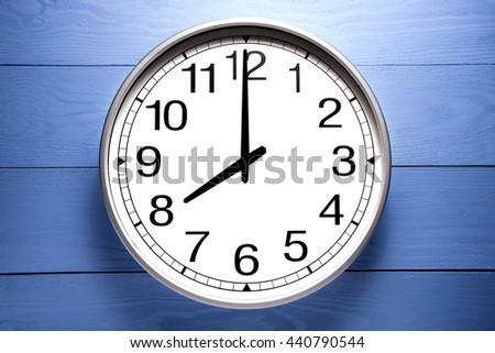Round clock shows shows at 8 o'clock, clock on blue background - stock photo