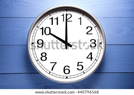 Round clock shows shows at 10 o'clock, clock on blue background - stock photo
