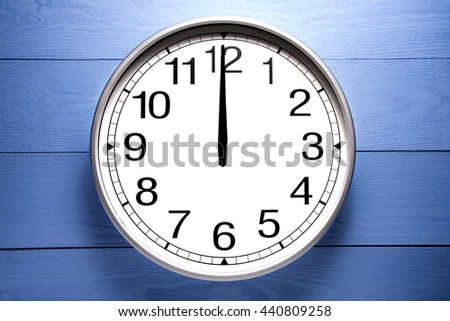 Round clock shows shows at 12 o'clock, clock on blue background - stock photo