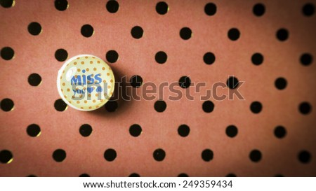 Round cute thumbtack or pushpin for whiteboard, notice board, gift card or special occasions with Miss You message on polka dot vintage patterns background. Slightly defocused and close-up shot - stock photo