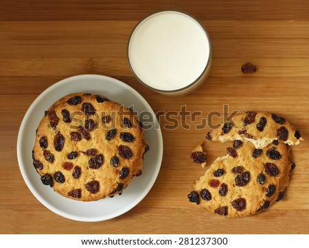 Round delicious cookies, Biscuits with raisins whole and broken down into two parts and a glass of natural milk on brown wooden background. Top view.