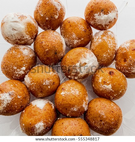 Round doughnuts dusted with powdered sugar