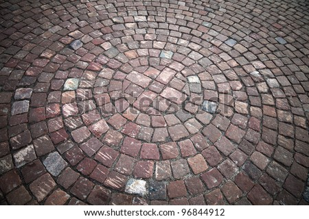 Round element of granite cobblestone road. Background texture