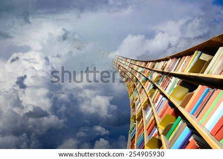 Round flying bookshelf against blue sky - stock photo