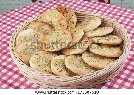 Round garlic flatbread in basket on red table - stock photo