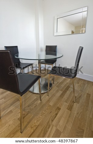round glass top dining table with leather chairs - stock photo