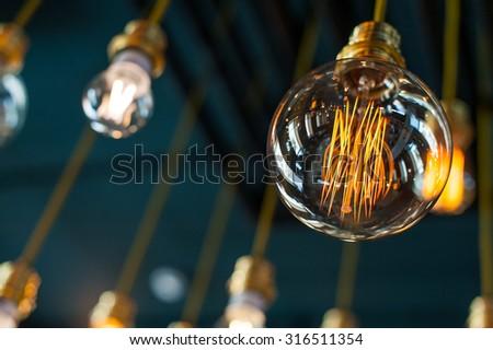 Round glowing tungsten lamp - stock photo