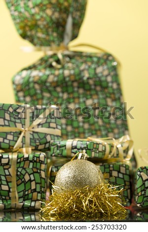 round gold Christmas ornament on the gold tinsel and gift boxes for background  - stock photo