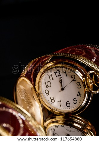 round gold watch with a tracery a red ribbon on a black background with reflection