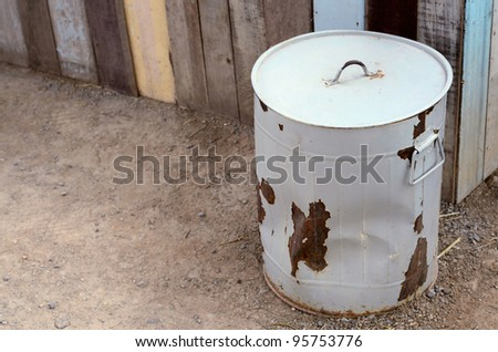 Round gray steel rust trash with lid on the ground - stock photo