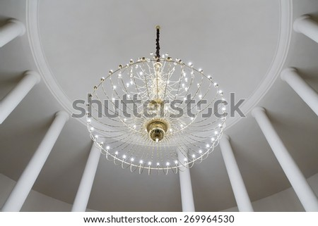 Round hall with columns and chandelier on the ceiling - stock photo