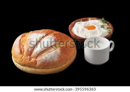 Round loaf of bread, milk in a Cup and the flour with raw egg on wooden plate with rosemary on black background