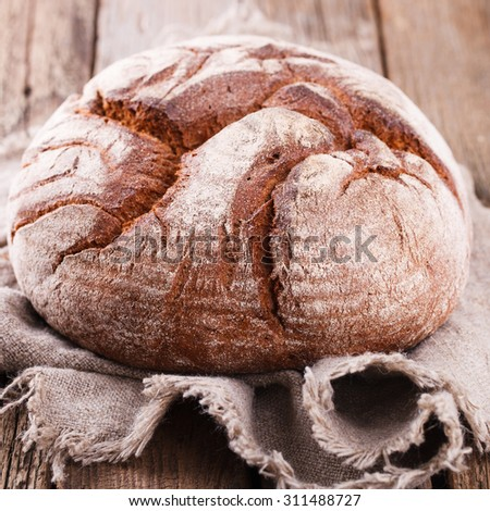 Round Loaf of Home made Bread made from rye, whole wheat flour and sourdough in rustic style, selective focus