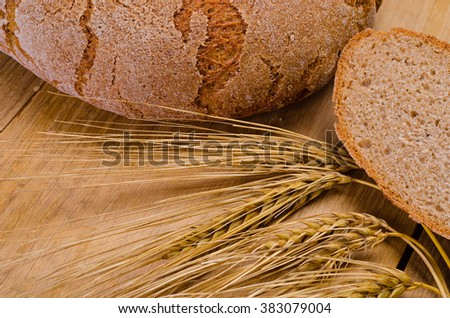 Round loaf of rye bread on a wooden table with ripe ears of wheat