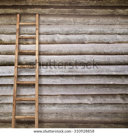 round log wall with a wooden ladder background