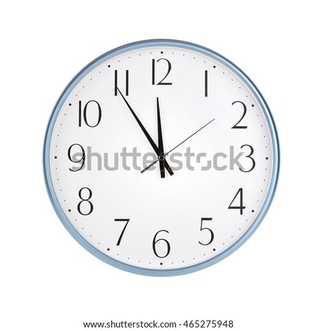 Round office clock shows five minutes to twelve