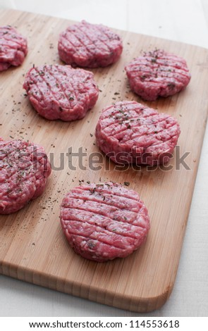 Round patties or chops from raw ground beef cooking vertical - stock photo