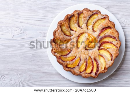 round peach pie on a wooden background horizontal view from above  - stock photo