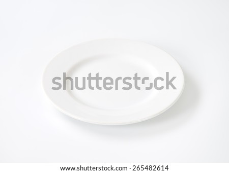 Round porcelain plate with rim - stock photo