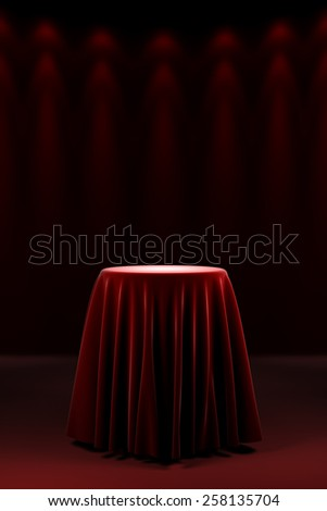 Round presentation pedestal covered with a red silk cloth in front of a wall illuminated by spot lights - stock photo