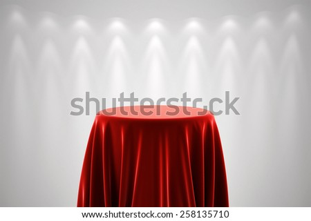 Round presentation pedestal covered with a red silk cloth in front of a white wall illuminated by a spot light - stock photo