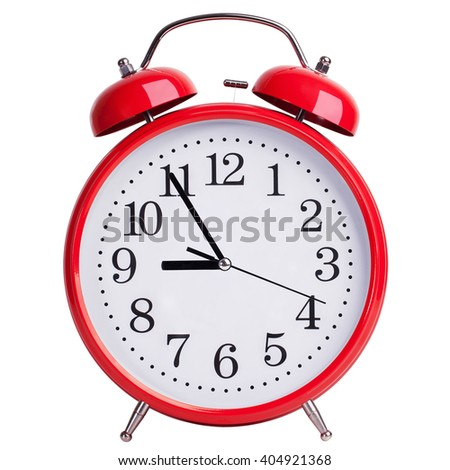 Round red alarm clock showing five to nine - stock photo