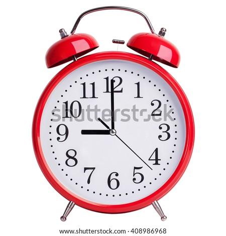 Round red alarm clock shows exactly nine o'clock - stock photo