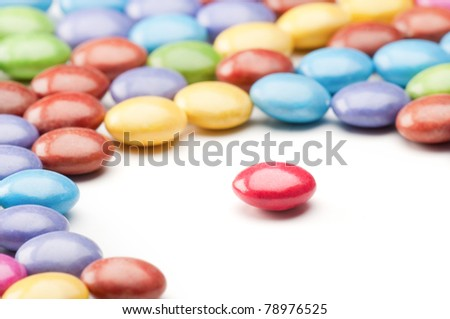 Round red candy isolated from other colorful candies - stock photo