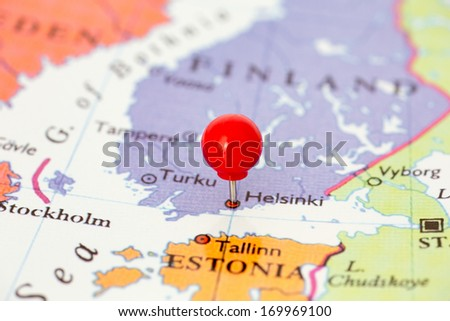 Round red thumb tack pinched through city of Helsinki on Finland map. Part of collection covering all major capitals of Europe.