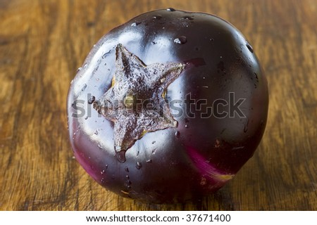 Round ripe eggplant on the preparation table - stock photo