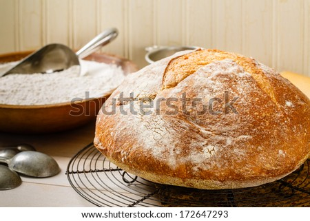 Round rustic artisan bread rests on a vintage wire cooling rack surrounded by a baking utensils and an old wood bowl full of flour