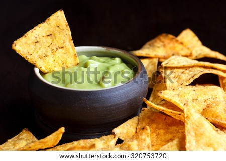 Round rustic brown bowl of guacamole dip surrounded with tortilla chips in perspective. Black background.