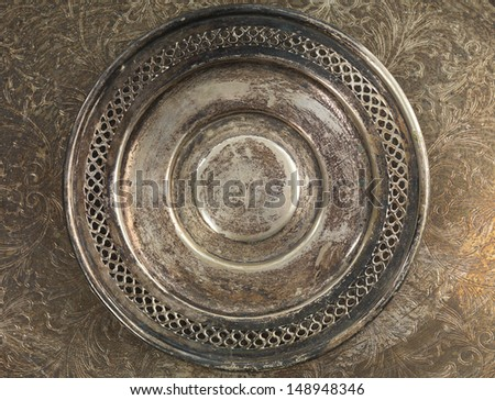 Round rustic silverware plate on metal background