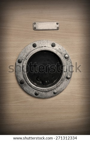 Round rusty ship porthole window with label. - stock photo