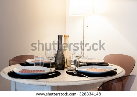Round set table in house rustic style light brown colors, lamp in background