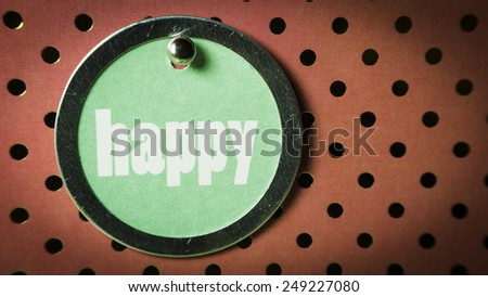 Round shape card attachment or badge pin for gift card or special occasions with metal clip and Happy text on black and red polka dot background. Slightly defocused and close-up shot. - stock photo