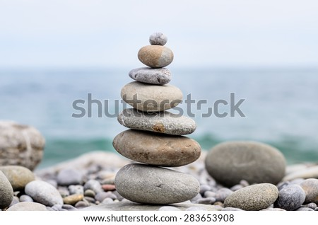 Round Smooth Stones Stacked According to Size on Tranquil Rocky Beach with View of Water in Background - stock photo